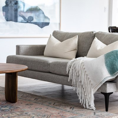 Grey couch with white pillows and white tasseled blanket in contemporary living room with round wood coffee table, framed art, and rug