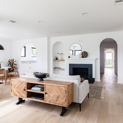 Contemporary living room with hardwood floor, white walls, grey couch, black fireplace, plants, and arched hallway