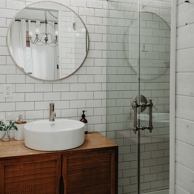 White tiled bathroom with wood vanity and glass door shower