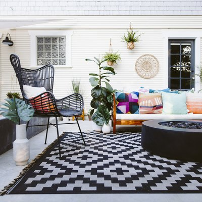 A colorful patio with modern seat and a black gas fire pit over a black and white rug