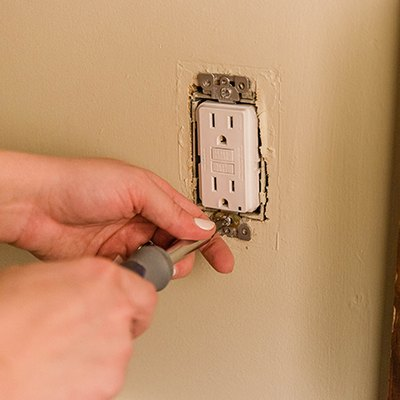 Person using a screwdriver to screw in place GFCI outlet