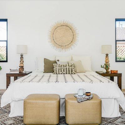 Bedroom with beige and white color scheme. A cube ottoman with teacups, a bed with beige-white bedding, woven wall hanging