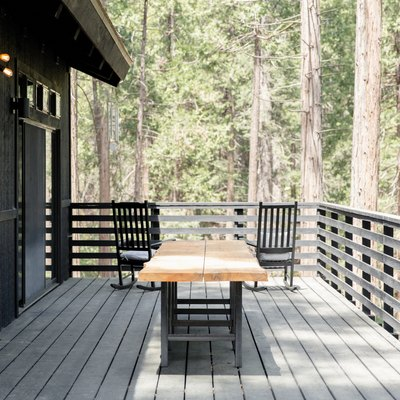 A wood picnic table and two black rocking chairs, on a deck of a black house. Forrest trees surround.