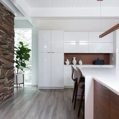 A stone wall and gray floor, in a Minimalist kitchen with white cabinets and a bar pendant light.