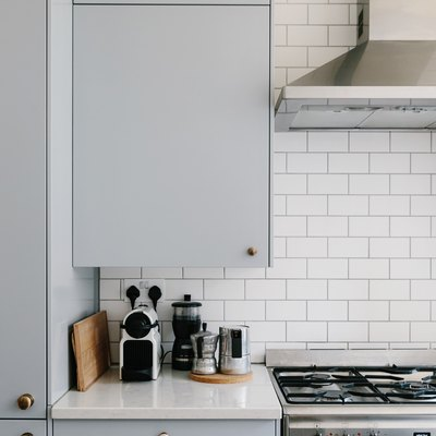 White tiled backsplash with grey kitchen cabinets, white countertops, silver stovetop, and various kitchen supplies