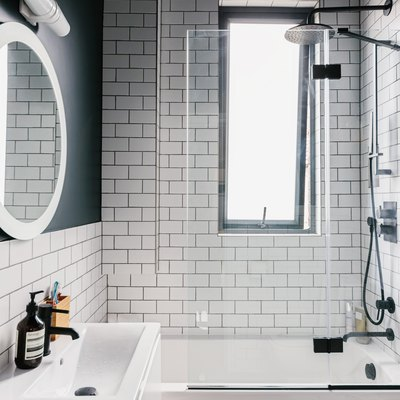 White-tiled bathroom with black ceiling, silver shower head, bathtub, and white sink with black faucet