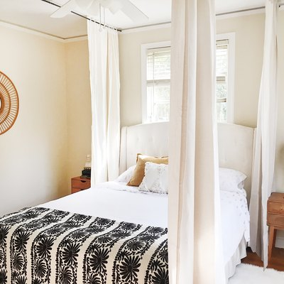 a bed with curtains hanging from the ceiling around it to create a canopy