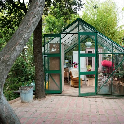 A green greenhouse in a backyard with a brick path and wood fence