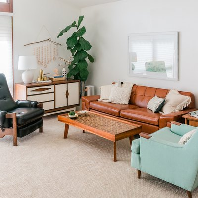 White walled-carpeted living room with retro leather and wood furniture