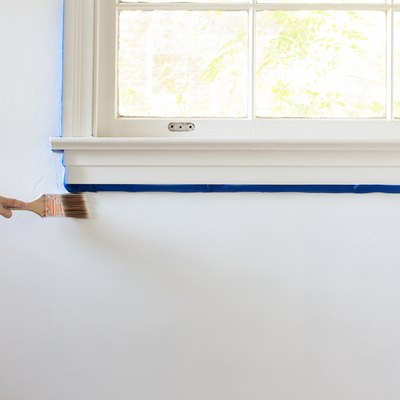 Hand painting white wall along edge of windowsill edged with blue painters tape
