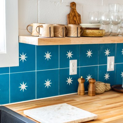 a kitchen wall with floating shelves that match the wooden countertop