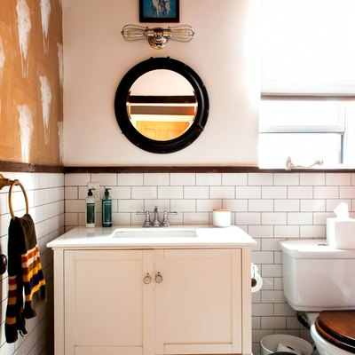 a bathroom with subway tile, a rustic wooden vanity and a cow-skull stencil patter on a wall