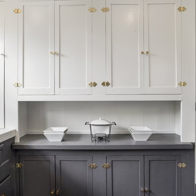 Kitchen cabinets with gray lower cabinets and white upper cabinets, brass fixtures.