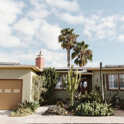 Front of midcentury home with palm trees