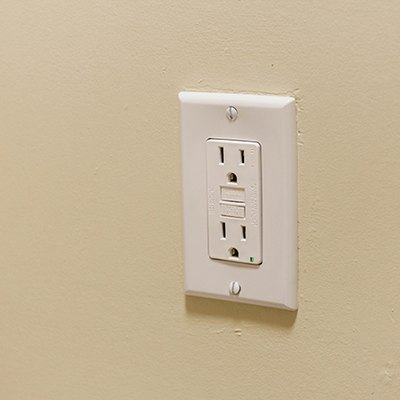 Wall GFCI outlet on a painted beige wall
