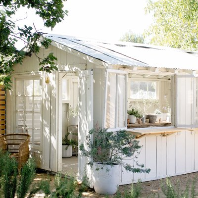 A white garden shed with open windows and shelf-like window sills