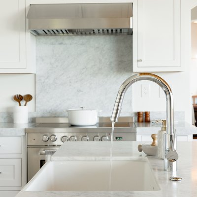 In a kitchen, a sink in a marble countertop, part of a kitchen island. The chrome faucet is running water. In the background, there's a chrome range with a white dutch oven on top.