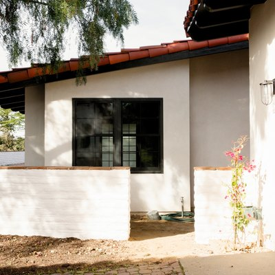 Spanish-style home with white walls and a clay tile roof. A light wood door, a side entrance to the house.