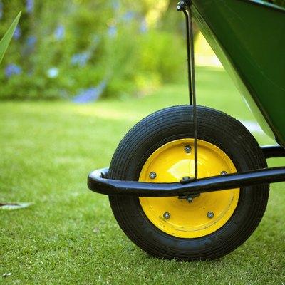 Close-up of the wheel of a wheelbarrow in a garden
