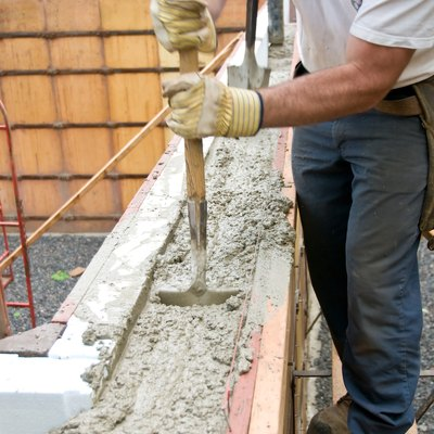 Construction worker stirring concrete inside mold