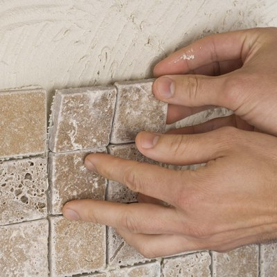 Person putting up tile on grout