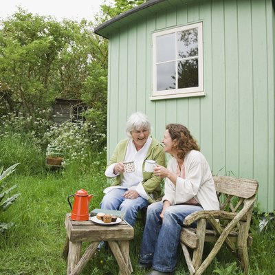 Mother and daughter sitting by garden shed