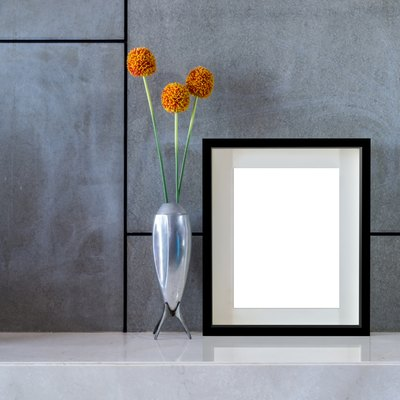 Modern interior wall with flowers vase and blank picture frame