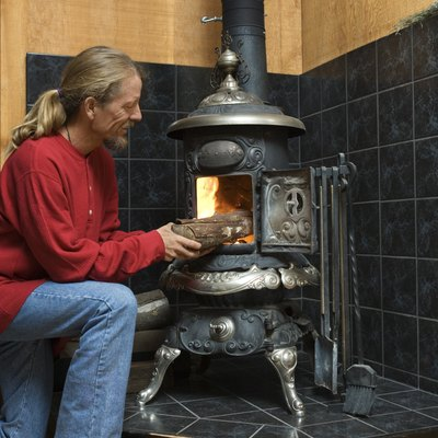 Man putting firewood into wood stove