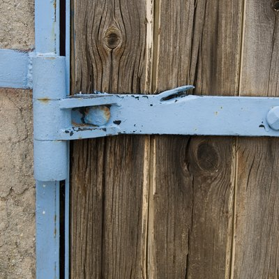 Detail of metal hinge on wooden door