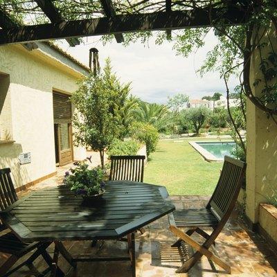 Hardwood garden furniture on terrace outside house