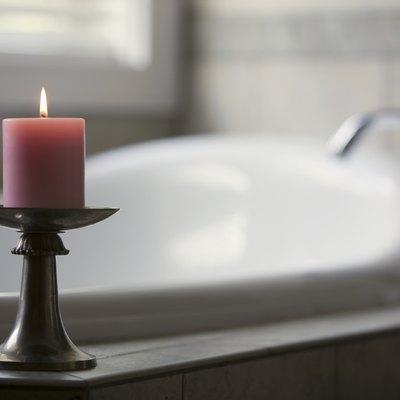 Pink candle burning beside bath tub in bathroom