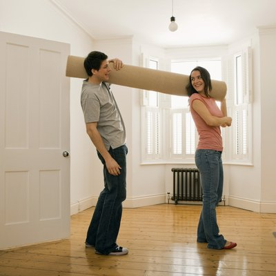Couple carrying carpet roll