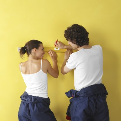 Man and woman holding level to wall