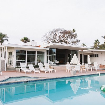 A white mid-century modern home with an in-ground swimming pool and a patio that has several white patio chairs