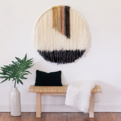 Round wall art hanging above bench