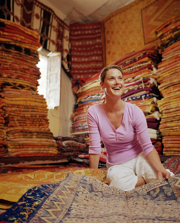 Woman looking at rug in rug shop, smiling