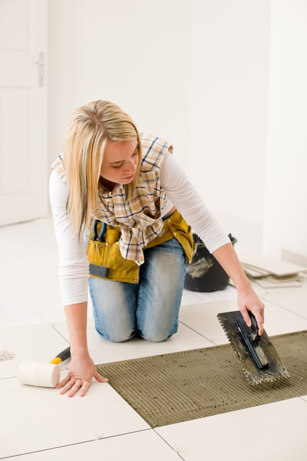 Home improvement, renovation - handywoman laying tile