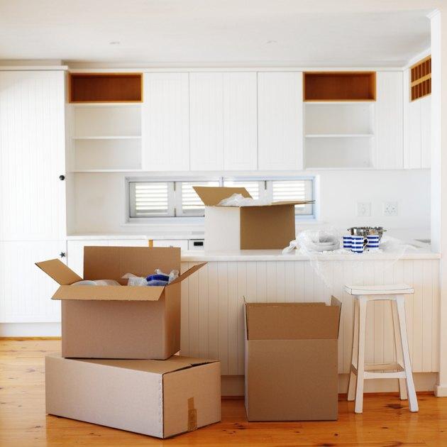Open cardboard boxes kept in an empty kitchen