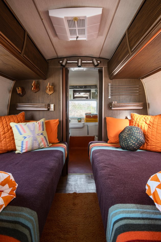 Twin beds with orange pillows and purple blankets inside the Airstream trailer.