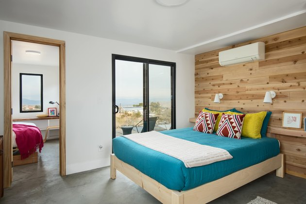 A bedroom with wood panel wall and slider door to outside.