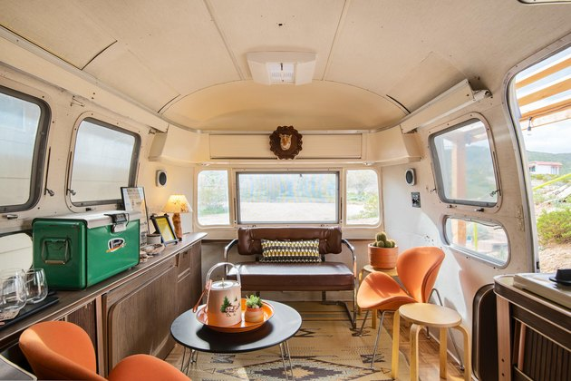 Inside the Airstream trailer seating area with mid-century chairs and vintage cooler.