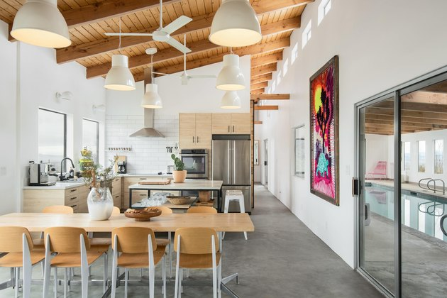 The kitchen and dining area with wood beamed ceiling and slider door to indoor pool.