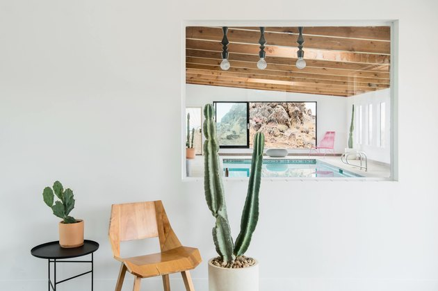 An interior window looking into pool area with wooden chair, side table and potted cacti.