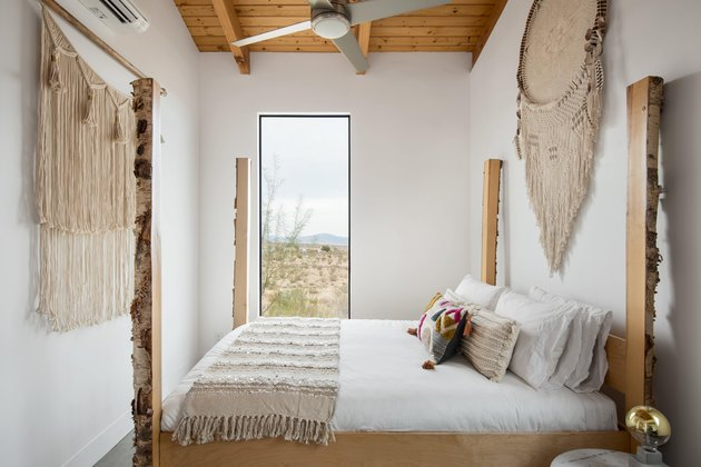 A bedroom with view featuring wall hangings and wood beamed ceilings.