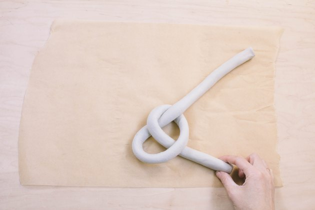 Shaping tube of air dry clay into a knot