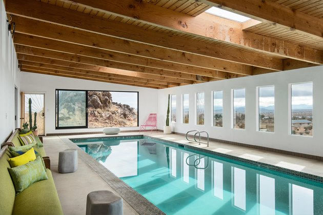 A wide shot of the indoor pool area with wood beamed ceilings, skylights, and large slider doors and windows.