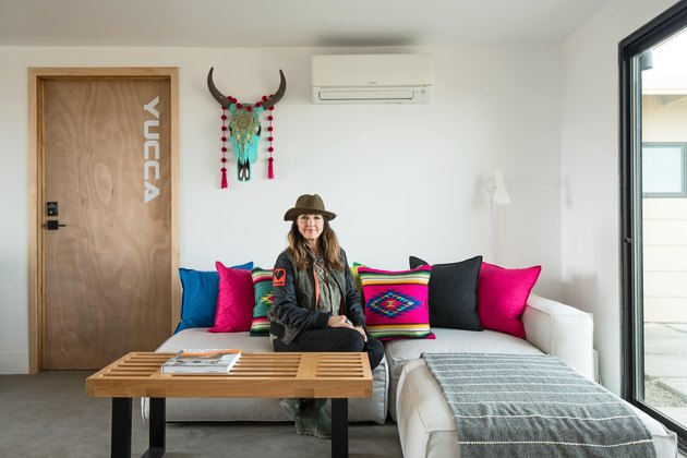 Kelly Van Patter sits on a sectional couch with colorful textile pillows in her desert home.