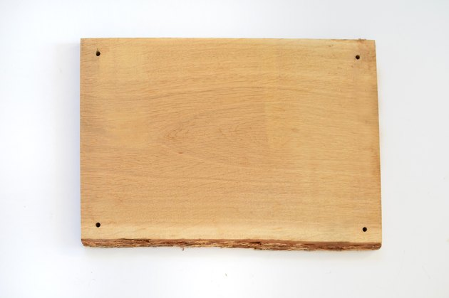 Piece of natural hardwood with a hole drilled through each corner