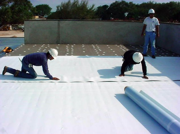 Laying TPO roofing sheets.