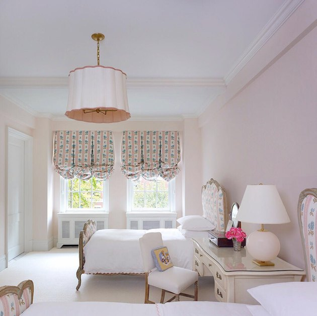 Victorian pink bedroom with feminine furnishings and upholstered headboard